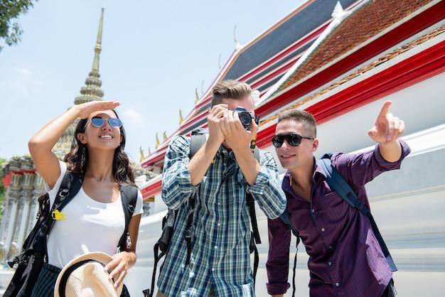 Gruppo di giovani amici di viaggiatore con zaino e sacco a pelo turistici al tempio a bangkok tailandia