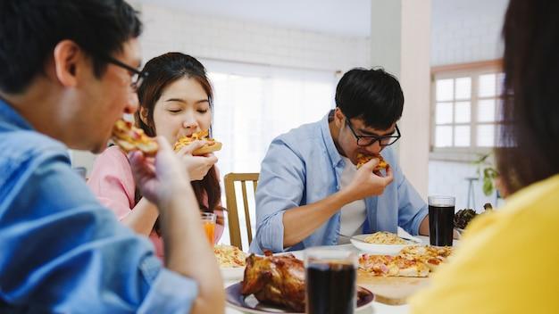 Gruppo di giovani amici felici a pranzo a casa. festa della famiglia asiatica che mangia pizza e che ride gustando un pasto seduti al tavolo da pranzo insieme a casa. celebrazione vacanza e stare insieme.
