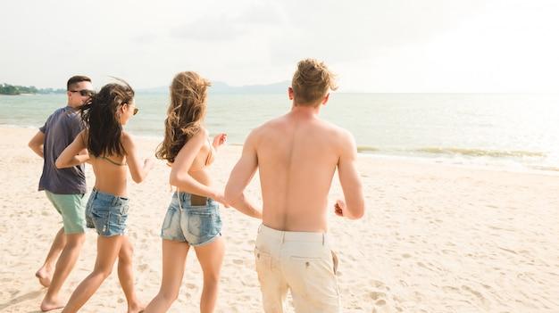 Gruppo di giovani amici felici che corrono dalla spiaggia al mare