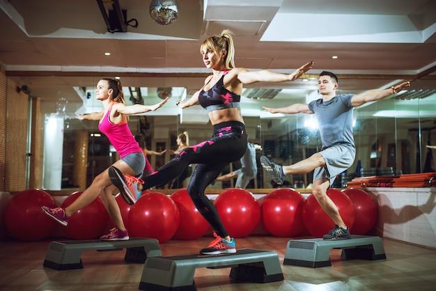 Gruppo di giovani attraenti belli sportivi attivi fitness persone accovacciate su una gamba sugli stepper a braccia aperte in palestra.