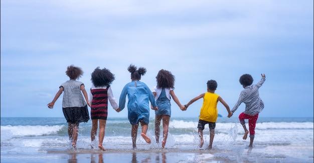 Gruppo di giovani bambini afroamericani che corrono sulla spiaggia.