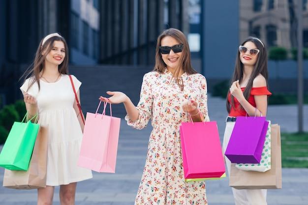 Gruppo di giovani belle ragazze felici in abiti casual, top e pantaloni che camminano dal centro commerciale con borse gialle, verdi, viola e rosa nelle loro mani.