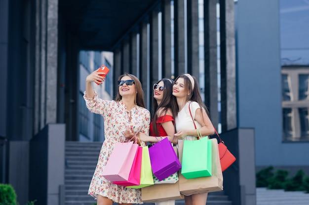 Gruppo di giovani belle ragazze in abiti casual con occhiali da sole, trucco, cerchio per capelli e borse della spesa colorate che fanno selfie dopo lo shopping di successo. piante da costruzione e parco in background