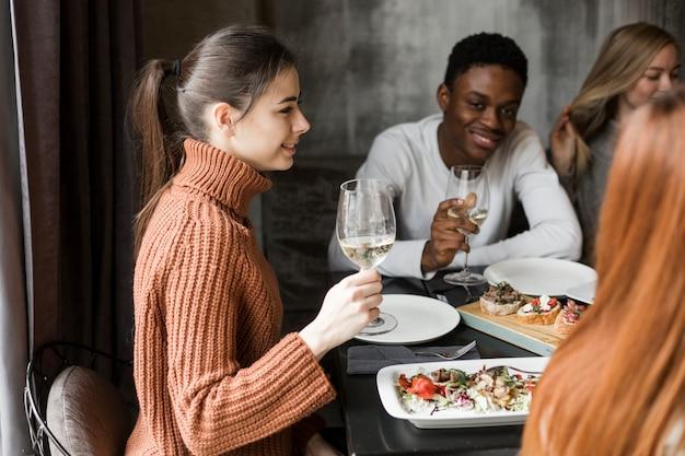 Gruppo di giovani che godono della cena e del vino
