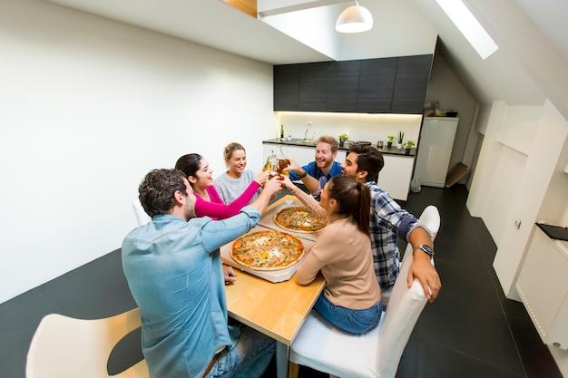 Gruppo di giovani che mangiano pizza e che bevono sidro nell'interno moderno