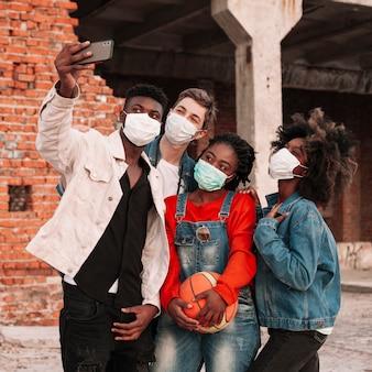 Gruppo di giovani che prendono insieme un selfie