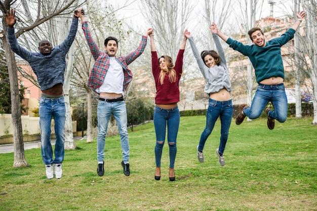 Gruppo di giovani che saltano insieme all'aperto