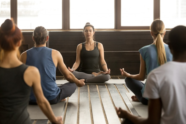 Gruppo di giovani che si siedono in sukhasana