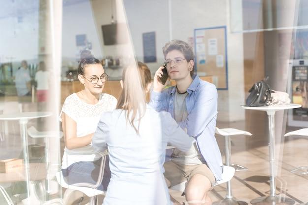 Gruppo di giovani che utilizzano il loro telefono cellulare a un coworking