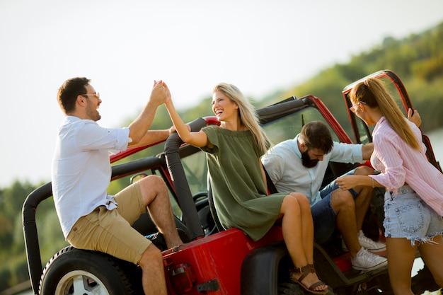 Gruppo di giovani divertirsi in auto all'aperto in una calda giornata estiva