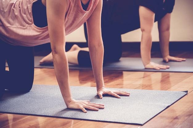 Gruppo di giovani donne asiatiche in buona salute che praticano lezione di yoga con l'istruttore in studio domestico