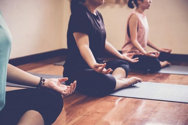 Gruppo di giovani donne asiatiche in buona salute che praticano lezione di yoga, posa del loto con l'istruttore in studio domestico.