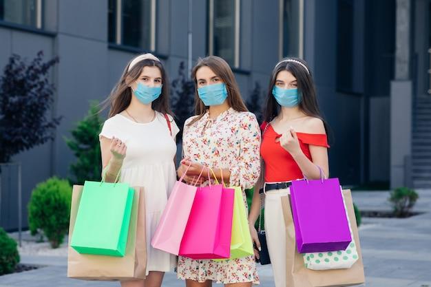 Gruppo di giovani donne che indossano maschere per proteggere la pandemia di coronavirus con borse colorate in mano. consumismo, acquisti, shopping, concetto di stile di vita.