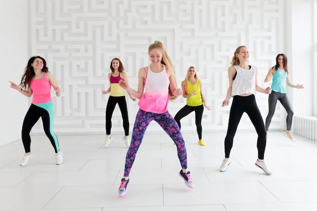 Gruppo di giovani donne felici in abiti sportivi alla classe di forma fisica di ballo nello studio bianco di forma fisica