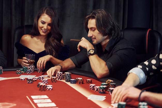Gruppo di giovani eleganti che giocano a poker nel casinò insieme