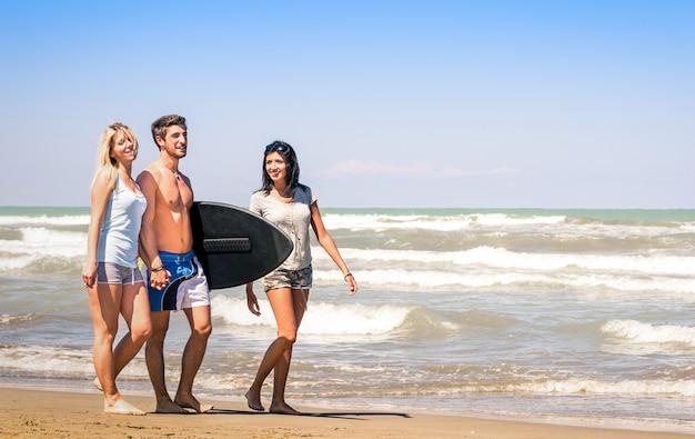 Gruppo di giovani felici sulle vacanze in spiaggia tenendo un tavola da surf