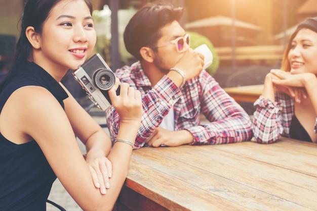 Gruppo di giovani hipster, seduto in un caffè, giovani amici allegri