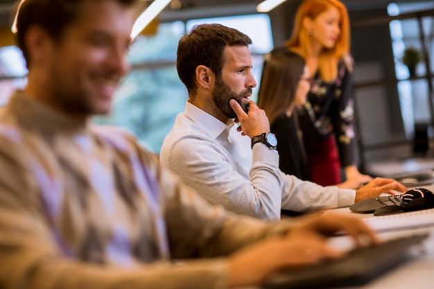 Gruppo di giovani imprenditori stanno lavorando insieme al desktop computer