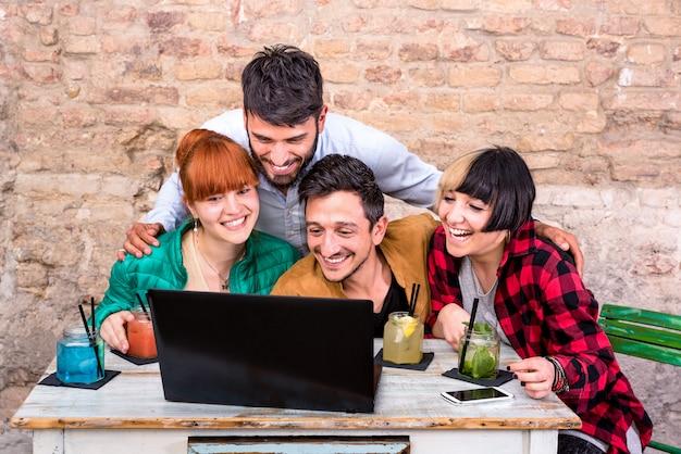 Gruppo di giovani migliori amici dei pantaloni a vita bassa con il computer in studio alternativo urbano
