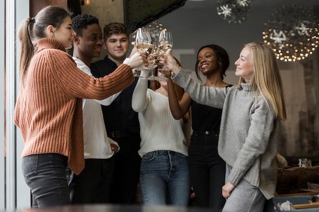 Gruppo di giovani positivi che tostano con il vino