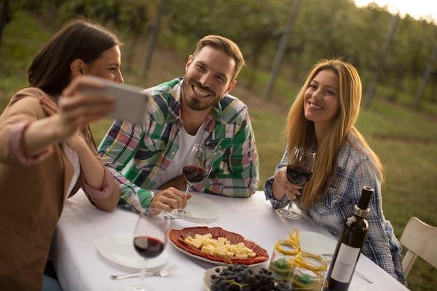 Gruppo di giovani seduti a tavola e bere vino rosso in vigna