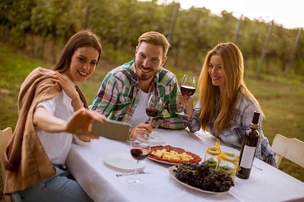 Gruppo di giovani seduti al tavolo e bere vino rosso in vigna