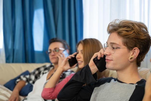 Gruppo di giovani seduti in fila su un divano a parlare con i loro telefoni cellulari