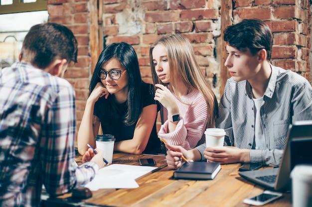 Gruppo di giovani seduti in un caffè, bere caffè e discutere nuove idee.