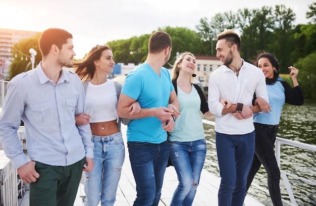 Gruppo di giovani sorridenti e di successo in vacanza sul molo.
