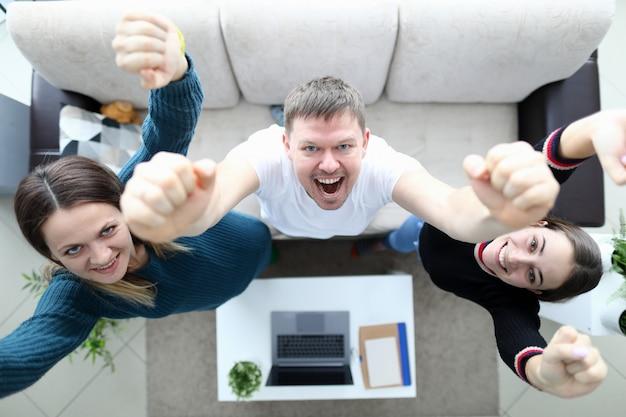 Gruppo di giovani sorridenti europei o gruppo che celebra la riuscita finitura del progetto con le mani sollevate in ufficio, vista dall'alto. motivazione, ispirazione aziendale, successo nel concetto di progetti