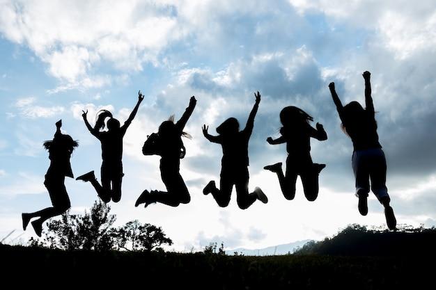 Gruppo di giovani sta saltando in cima alla montagna