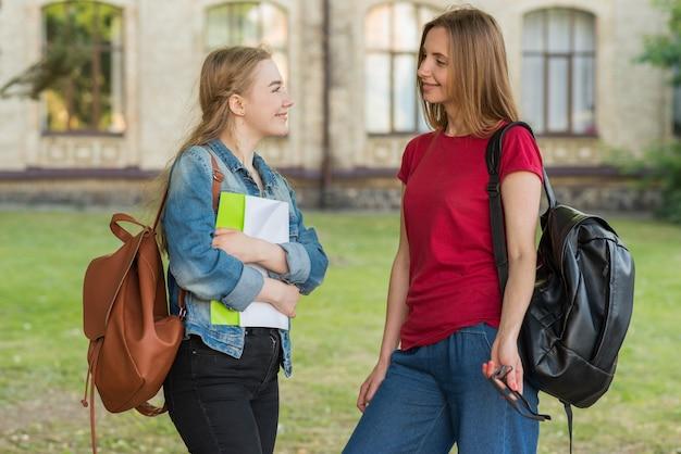 Gruppo di giovani studenti di fronte all'edificio scolastico