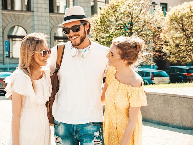 Gruppo di giovani tre amici alla moda che posano nella via. moda uomo e due ragazze carine vestite in abiti estivi casual. modelle sorridenti divertendosi in occhiali da sole. donne allegre e ragazzo che chiacchierano