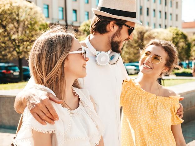 Gruppo di giovani tre amici alla moda che posano nella via. moda uomo e due ragazze carine vestite in abiti estivi casual. modelli sorridenti divertendosi in occhiali da sole. donne allegre e ragazzo che impazziscono