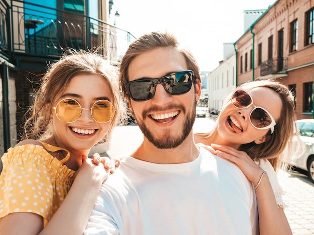 Gruppo di giovani tre amici alla moda in strada. uomo e due ragazze carine vestite in abiti estivi casual. modelli sorridenti che si divertono in occhiali da sole. donne e ragazzo che fanno foto selfie su smartphone