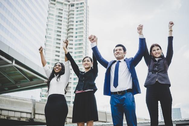 Gruppo di giovani uomini d'affari con le mani in aria successo sui loro piani.
