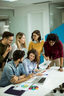 Gruppo di giovani uomini d'affari multietnica lavorando e comunicando insieme in ufficio creativo