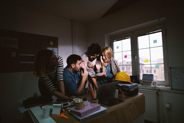 Gruppo di giovani uomini d'affari stanchi festeggia dopo aver trovato una soluzione al problema durante il soggiorno dopo il regolare orario di lavoro nell'ufficio buio.