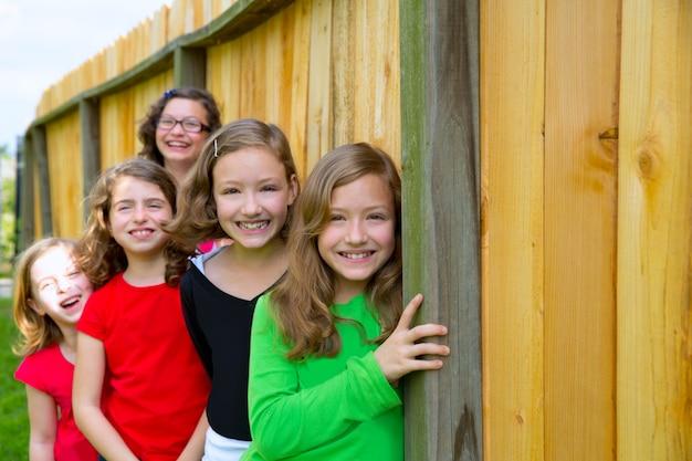 Gruppo di grils in una fila che sorride in una rete fissa di legno
