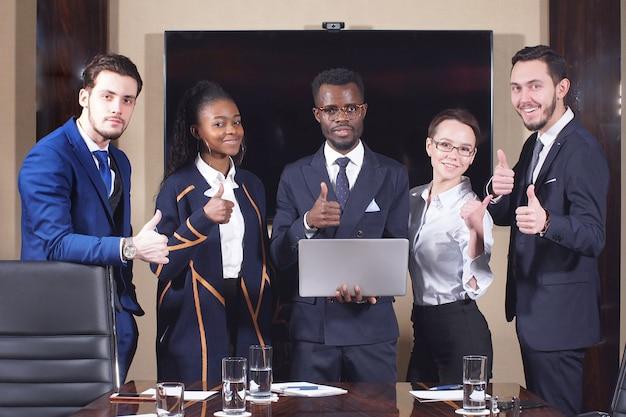 Gruppo di gruppo di affari che sta nell'auditorium che dà i pollici su mentre esaminando macchina fotografica