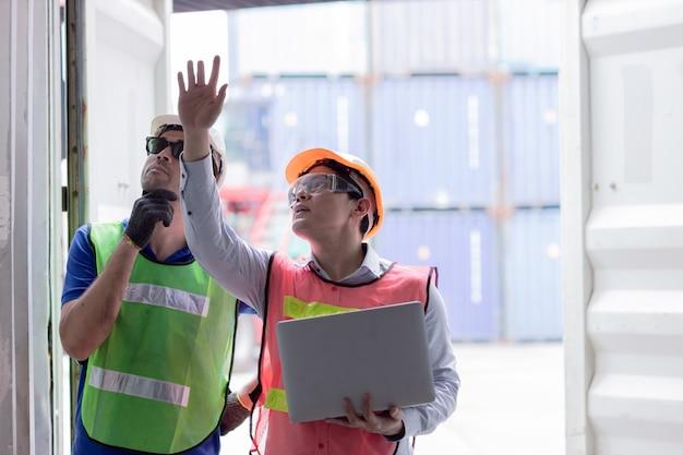 Gruppo di ingegneri di audit di lavoro nel porto di spedizione che controlla il test di resistenza del contenitore di carico delle merci per la sicurezza e la protezione secondo lo standard dei contenitori intermodali.