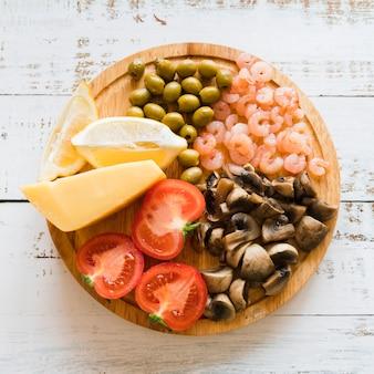 Gruppo di ingredienti italiani di vista superiore sul piatto di legno
