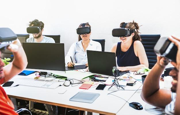 Gruppo di lavoratori degli impiegati dei giovani divertendosi con gli occhiali di protezione di realtà virtuale del vr nello studio startup