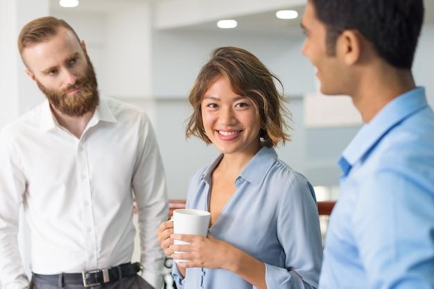 Gruppo di lavoro multietnico che chiacchiera durante la riunione corporativa