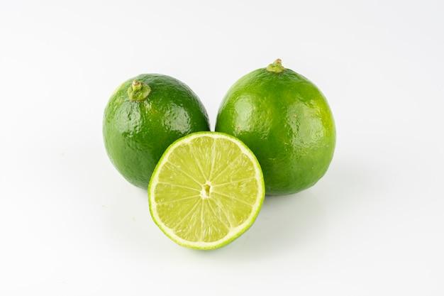 Gruppo di limoni verdi con il limone affettato sopra fondo bianco.