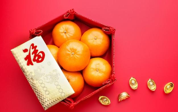 Gruppo di mandarino in vassoio e busta pacco ang pow con lingotti d'oro sul piano del tavolo rosso