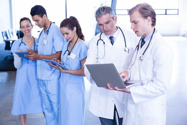 Gruppo di medici che discute e che utilizza computer portatile e compressa digitale nell'ospedale