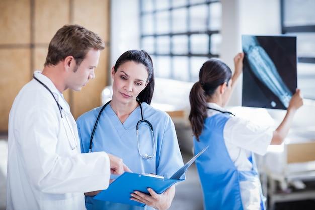 Gruppo di medici che discute il rapporto sulla lavagna per appunti all'ospedale
