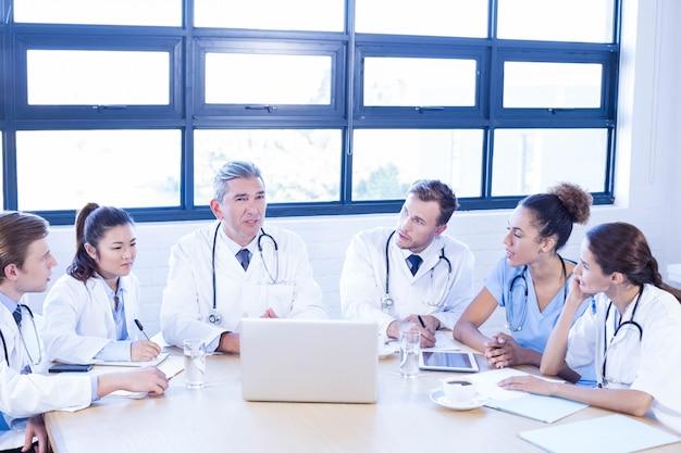 Gruppo di medici che discute nella riunione ad una sala per conferenze