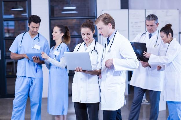 Gruppo di medici che discute rapporto dei raggi x e che utilizza computer portatile e compressa digitale nell'ospedale